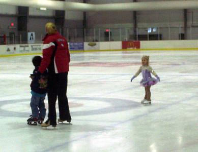 Rachel skates while Coach Jenny helps Nolan learn to skate.