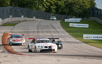 The #55 BMW M3 leads the #44 Flying Lizard Porsche into turn 5 as the #055 LMP2 prepares to pass.