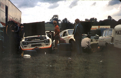 Regular pre race maintenance in the pits which I think was at Oulton Park. facing bove drivers door is David Broad, Ralphs son, LH wheel work is Tivvy (Carl) Shenton, directly above the LH wheel arch in background is Clive Parker, stood up in the orange overall is Bill ???, stood watching with blue stripe is Terry Goldstone behing him lying back on the ground under the other car is Graham Goode