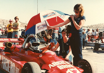 Anne holds an umbrella for shade while Patty kneels at the side and Mike Murphy does one last tire pressure check on the left rear.