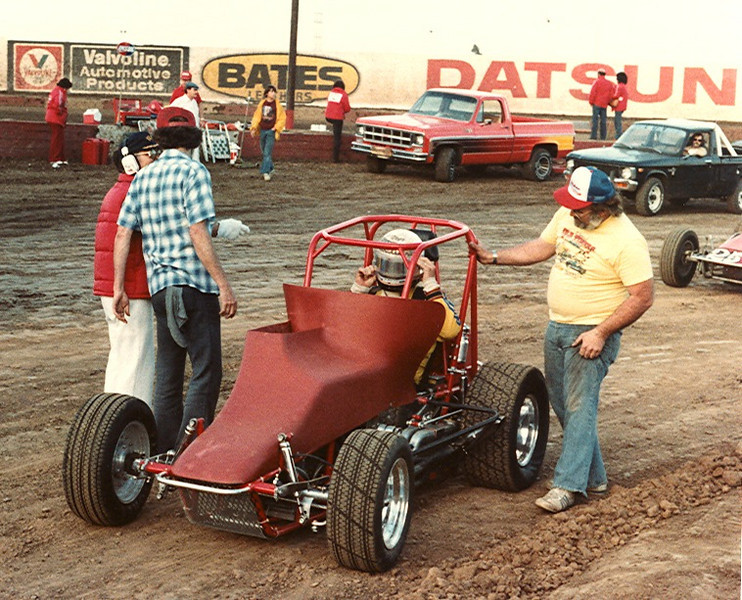 At Ascot Park this was the first test with the Larry Howard-Ron Weeks built Midget with the 2 litre Cosworth BDP engine. The throttle barrel assembly was positioned vertically hence the opening at the top of the hood. Ron is in the yellow T Shirt.
