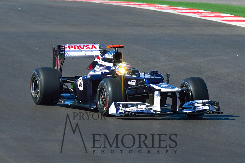 Sun reflecting off the gold visor of Pastor Maldonado driving the #18 Williams F1 car.