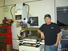 Steve Hendren stands next to his new digital valve-seating machine.