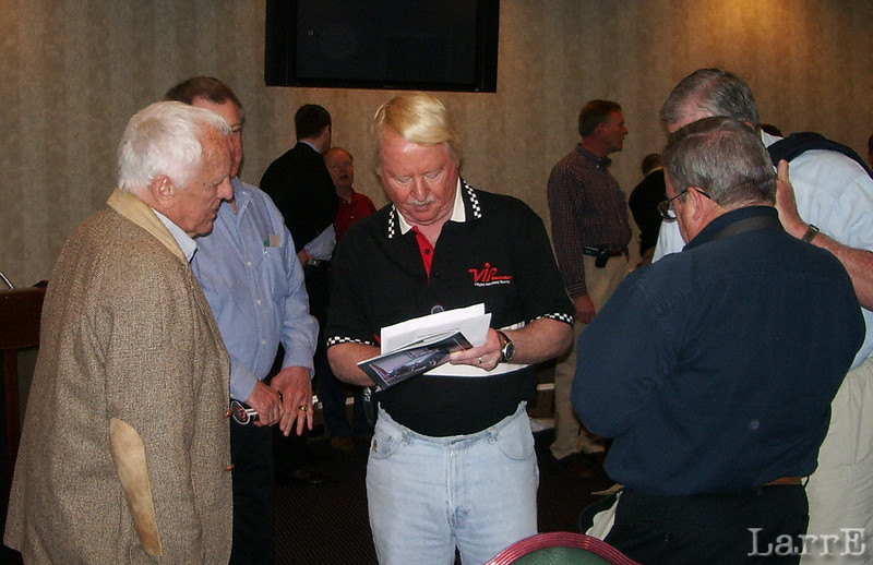 On the day before the Kasey Kahne press meeting I attended the monthly Walter Mitty Sports car luncheon. It was in the very same Lowes Speedway room that would be used today for the Kahne press conference. Here Bill Neely, the author of many books on racing,looks on as checks list of over 20 book Bill has written
