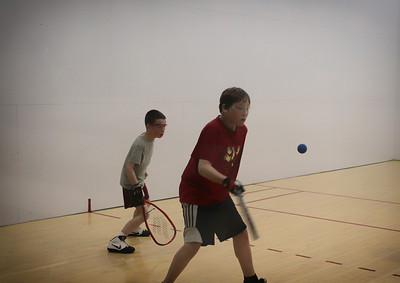 Spencer Zidek gets ready to hit a forehand shot as Alex Wright looks on..