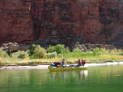 Gary, Eric, and Olaf enjoying the day in a yellow boat on a green river with red rock walls.