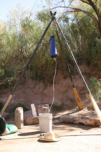 We must filter the river water every day, to make drinking and cooking water.  Here, we are using the boats' oars to hang the water bag.  It filters into one of our 6 tan-colored 6-gallon jugs.