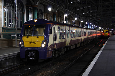 334012 sitting at Platform 15 of Glasgow Central, waiting to depart on a service to Ayr. It is partially repainted in Scotrail blue, and still retains SPT maroon and cream due to a lack of trains