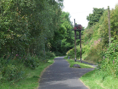 Looking west along the trackbed towards Kilmacolm from Route Marker 15, just to the west of Bridge Of Weir station, on the cycle track that sits on the trackbed. This is one of the sculptures that are dotted around the trackbed, either historical or railway related