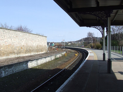 Forres Station looking towards Aberdeen. The large goods yard at the station was behind the wall to the left. The photograph is taken from the former P2, with the old P3 to the left. P1 was the Aviemore and Perth platform, and is now where the station car park is located.