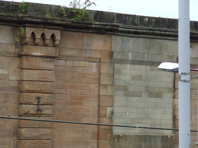 The bricked up entrance in the wall at Greenock Central to the right shows where Bogle Street crossed the station on a pedestrian bridge, along with still intact bridge number(9B) and roof beam support. The bridge was removed during station refurbishment work as it was unsafe. It is obvious from this picture that either the wrong type of sandstone was used, or it is concrete bricks that were coated, and has since lost the coating, to blend in with the sandstone surrounding