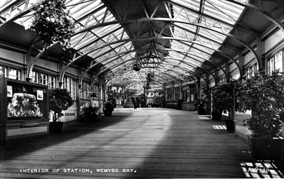 Wemyss Bay Station, standing in the walkway to the steamers and pier. It was part of the Greenock & Wemyss Bay Railway and later Caledonian Railway. The line opened in 1865 and remains open. It was designed to allow trains from Glasgow to connect to steamers to the Clyde resorts at Wemyss Bay, and branches off the Glasgow, Paisley & Greenock Railway at Port Glasgow. The line was built as competition to the Glasgow & South Western Railway routes to Greenock, Largs and Ardrossan. The station was opened in 1865 and rebuilt with the current building in 1902.