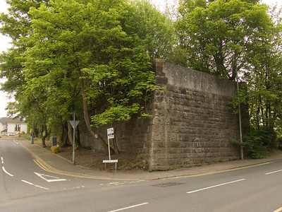 Junction of Corsebar Road and Victoria Road in Paisley. The is the remaining abutment of the bridge that crossed here on the G&SWR Barrhead Branch (Potterhill Branch) that came from Meiklerigs Junction where it connected to the Paisley Canal Line via Corsebar Junction and Potterhill Junction. The Potterhill Branch opened in 1902 as a circular route from St Enoch to Barrhead via Paisley and the Glasgow, Barrhead and Paisley Joint Railway (and was to be in competition with the Caledonian Railway Paisley & Barrhead District Railway). However, this only lasted until 1907 when it was discontinued, and trains contiued to Barrhead via Nitshill, and via Paisley to Barrhead Central. The line from Potterhill to Barrhead closed in 1913 to passengers, and in 1917 the route closed completely to passengers. Bus and tram use meant the line was never popular and it was unprofitable. This was the same reason the Caledonian route was never used by passengers. In 1909 Corsebar Junction to Barrhead was singled and the signal boxes closed meaning Meiklerigs Junction was abolished and Potterhill Junction on the Paisley Canal Line was closed and lifted. The Potterhill Branch lasted until 1970, being used for freight during this time.