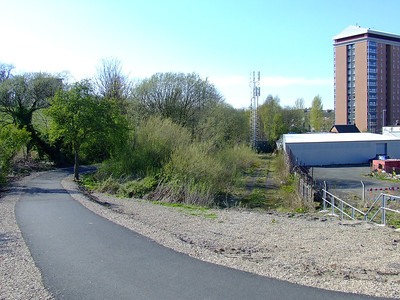Looking West towards Paisley West Station. The photo was taken on the cycle track that sits on the majority of the trackbed at Camphill near Paisley Canal. There was a railway bridge here, but it was dismantled when the line closed in 1983. Here the trackbed runs along the centre right of shot, blocked by the mobile telephone mast.