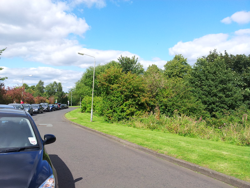 Stranka Avenue in Paisley, close to the Lord Lounsdale pub in Lounsdale Road. The trees in the picture sit on the trackbed that ran came from Meiklerigs Junction where it connected to the Paisley Canal Line via Corsebar Junction and Potterhill Junction. The Potterhill Branch opened in 1902 as a circular route from St Enoch to Barrhead via Paisley and the Glasgow, Barrhead and Paisley Joint Railway (and was to be in competition with the Caledonian Railway Paisley & Barrhead District Railway). However, this only lasted until 1907 when it was discontinued, and trains contiued to Barrhead via Nitshill, and via Paisley to Barrhead Central. The line from Potterhill to Barrhead closed in 1913 to passengers, and in 1917 the route closed completely to passengers. Bus and tram use meant the line was never popular and it was unprofitable. This was the same reason the Caledonian route was never used by passengers. In 1909 Corsebar Junction to Barrhead was singled and the signal boxes closed meaning Meiklerigs Junction was abolished and Potterhill Junction on the Paisley Canal Line was closed and lifted. The Potterhill Branch lasted until 1970, being used for freight during this time.