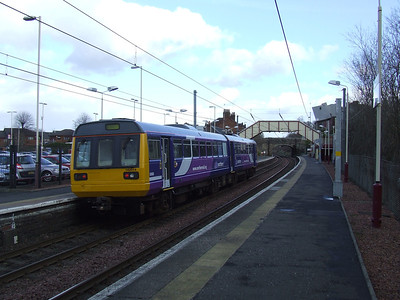 142014 passing through Johnstone en route to Glasgow Works in Springburn for an overhaul. The Class 142 is barred from using the West Coast Main Line, so uses the Glasgow & South Western route from Dumfries to Kilmarnock and from there either using the Ayr main line via Barassie or running via Barrhead.