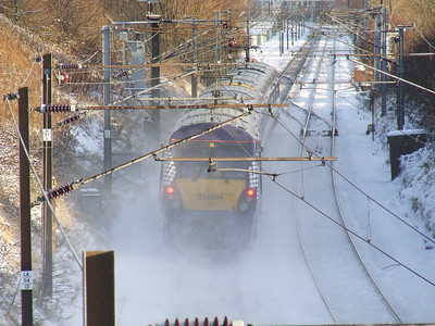334006 at the rear of a Glasgow Central service kicking up snow as it passes through Elderslie