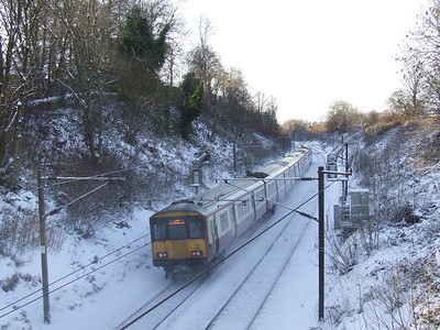 318255 at the rear of a Largs service kicking up snow as it slows while approaching Johnstone station