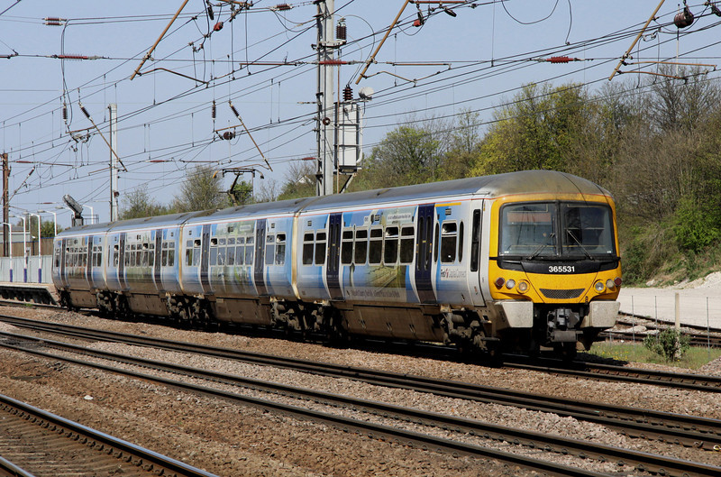 9 April. Carrying Nelson's County Norfolk promotional livery, 365531 leaves Hitchin with the 1145 Peterborough - King's Cross.