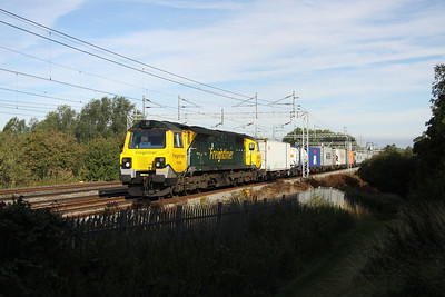 20 August. Shadow and sun as 70008 is illuminated passing Bradwell on the 4L97 0459 Trafford Park - Felixstowe.