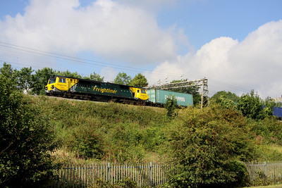 19 August. An elevated 70008 is seen passing alongside Haversham Road approaching Wolverton in charge of the 4L97 0503 Trafford Park - Felixstowe.