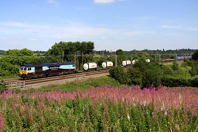 10 August 2012. Epilobium Angustifolium or Rosebay Willowherb if you prefer dominates the foreground at Chelmscote as uniquely liveried 66434 passes with the 4M71 1054 Purfleet - Daventry.