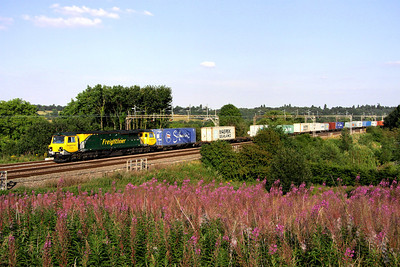 10 August. A lucky image as not only had the sun just appeared from behind a cloud but Pendolinos were approaching from both the north and south. 70020 leads 4M93 1330 Felixstowe - Lawley Street past Chelmscote.
