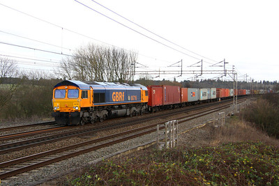 7 January. Full gloom now as 66716 LOCOMOTIVE & CARRIAGE INSTITUTION CENTENARY 1911-2011 with its distinctive round nameplate passes Chelmscote with the 4M23 1017 Felixstowe - Hams Hall.