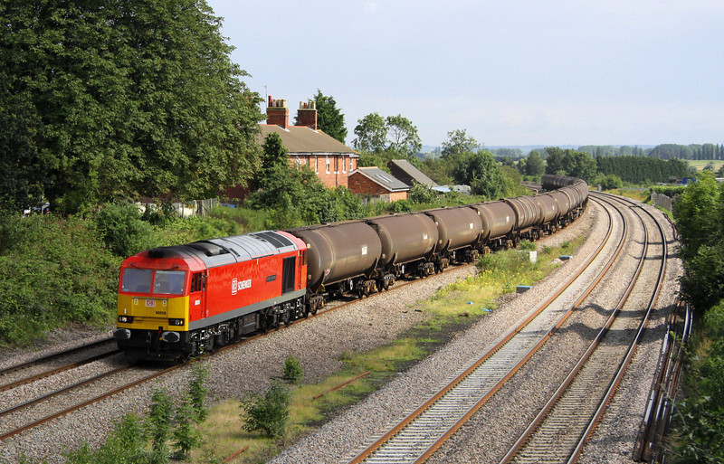 14 July. Just about in the sun, former Loadhaul legend, 60059 Swinden Dalesman passes Hartops Bridge, Oakley with the 6E38 1310 Colnbrook - Lindsey OR empty tanks.