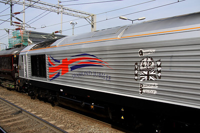 23 March. The bodysides of 67026 are embellished with a stylised 'fluttering' union jack flag and Diamond Jubilee wording along with the official Diamond Jubilee logo as designed by 10 year old Katherine Dewar from Chester. Her design won a Blue Peter competition which attracted over 35,000 entries and depicts a crown on top of a union jack flag flanked by two columns each containing three diamonds. Each diamond is representative of 10 years rule.