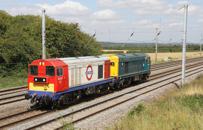 15 August 2015. Colourful choppers as 20205 in BR blue with small a small Eastfield  dog on her bodyside partners underground liveried 20227 as the duo head north past Millbrook Bridge working the 0Z20 1015 Ripple Lane - MRC Butterley.