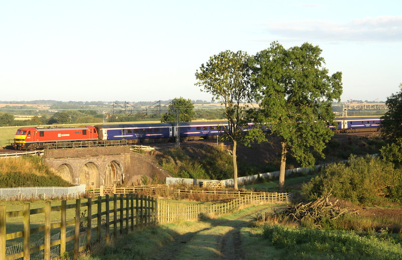 28 August 2015. Sunny skoda as 90036 Driver Jack Mills bursts past Three Arches, Castlethorpe with the overnight Highland sleeper, the 1M16 2044 Inverness - Euston.
