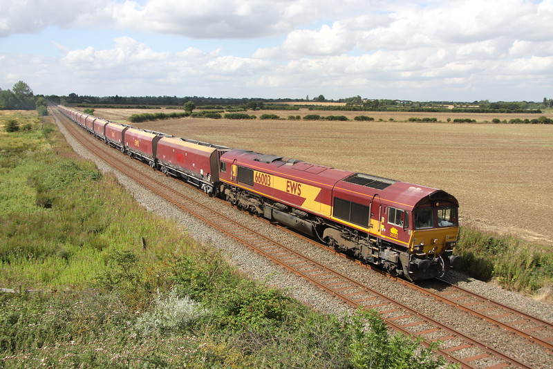 15 August 2015. 66003 with a spare HTA set of wagons passes Husbourne Crawley heading towards Ridgmont station with the 6H10 1215 Bletchley - Peak Forest empty stone.