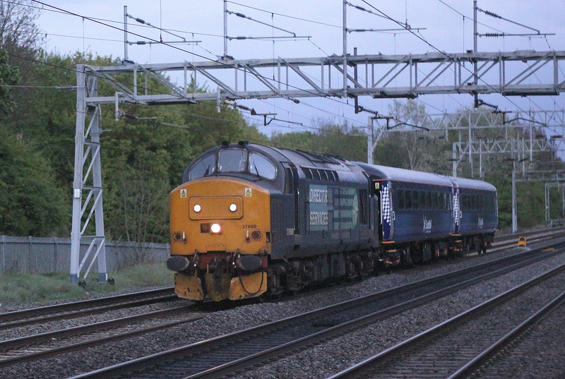 1 May 2015. A high ISO setting was required in poor light to capture 37688 Kingmoor TMD passing Bradwell with two Mark 2 vehicles namely 6137 + 5955 which have been repainted into Scotrail livery for the loco hauled Fife Circle services around Edinburgh. The repainting was carried out at Eastleigh Works and 5955 formerly carried Virgin colours whereas 6137 wore Arriva blue. This working being the 1927 Willesden Brent - Crewe Coal Sidings.