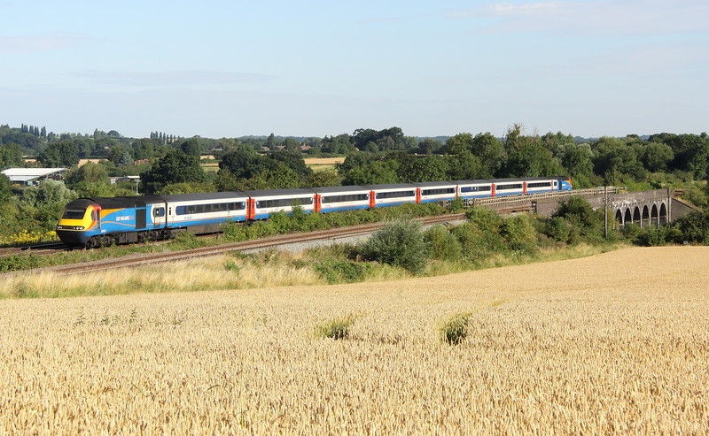 1 August 2016. 43043  passes the unharvested field at Oakley with the 1C15 0525 Leeds - St Pancras International. 43043 was formerly named LEICESTERSHIRE COUNTY CRICKET CLUB.
