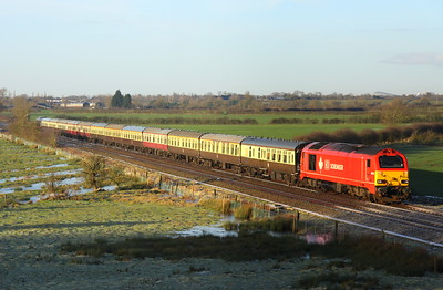 28 December 2017. With frost still hanging in the shadows, maple leaf 67018 Keith Heller passes Husborne Crawley leading the Pieman One, the 1Z82 0843 Euston - Old Dalby. The Xscape building in Central Milton Keynes is visible on the horizon directly above the leading cab of 67018.