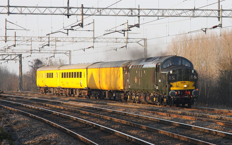 22 January 2017. Queen of green, 37057 is seen dancing with the shadows as she approaches Wolverton with the 1Q06 1235 Derby RTC - Old Oak Common.