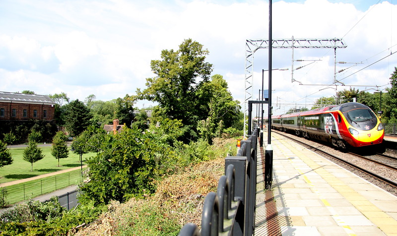 1 September 2017. Tree clearance next to platform 1 at Wolverton has created a clear view across Wolverton Park towards the former Royal Train shed (far left). 390040 Virgin Radio Star passes by on the 1A27 1115 Manchester Piccadilly - Euston.