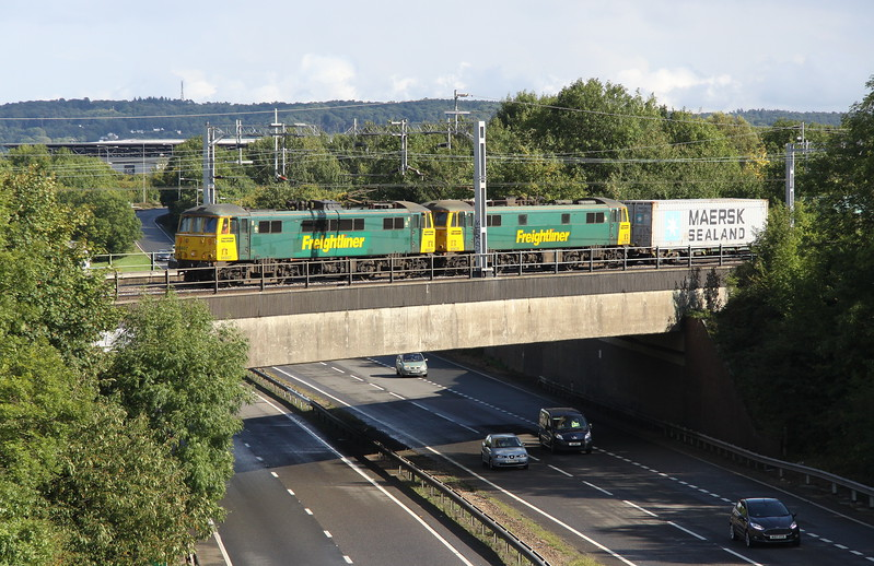 8 September 2017. With Brickhill woods and stadium: mk, the home of MK Dons behind, 86607 + 86628 cross the A5 at Granby just north of Bletchley whilst working 4M88 0932 Felixstowe - Crewe.