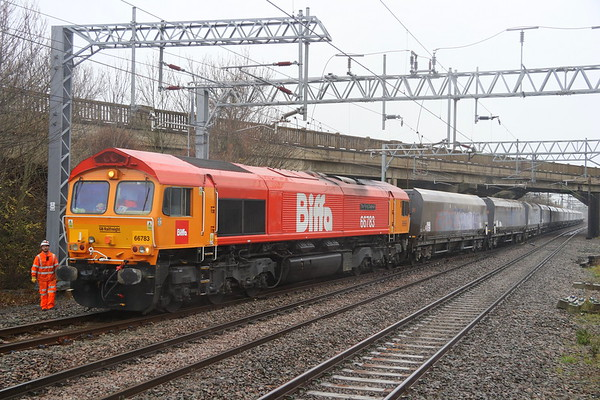 1  December 2018. Shades of orange on a gloomy day. 66783 The Flying Dustman stands with her train, the 6H11 1133 Bletchley CEMEX - Wellingborough Yard underneath Bletchley flyover having reversed out of the stone terminal. Note the additional front light and drawgear from her previous Lickey Banker duties when numbered 66058.