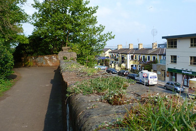 Looking along the pathway built on the former line. The line continued across the road on the bridge where the tree now stands. The yellow building with the four chimney stacks is the railway station.