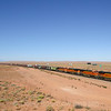 An Eastbound unit grain train is seen arriving in Winslow. Some 60 miles to the West the 12,633 foot San Francisco Mountain looms over the desert. The peaks are partially obscured by a residual haze from ongoing wildfires in California, 10-10-20.