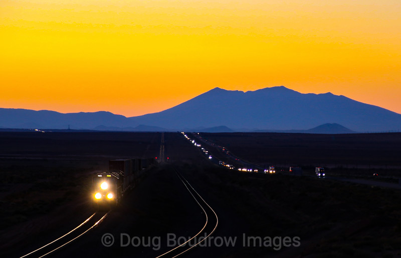 """After arriving in Winslow for a stay at La Posada, it seemed like the only logical move would be to go to """"The Bridge."""" As we pulled in the light was just about done but a hotshot Eastbound stack train was closing in. With a handful of seconds to spare, I had no time to play with settings so I just winged it. The haze from the wildfires hangs in the air creating an orange glow, 10-9-20."""