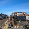 Pan AM Railways LOSA highballs South through Winchester Center splitting the old Boston & Maine searchlight signals just North of the Station. The train has 28 empty gondolas bound for the Wynn Casino construction project in Everett, 2-21-17.