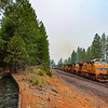 An Eastbound intermodal train is seen passing Gold Run on the way up to Donner Pass. The smoke from the Dixie Fire was thick causing the air to be hazy, 8-18-21.