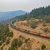 An Eastbound Union Pacific Z train is seen rounding the curves in Casa Loma above the American River Canyon. The smoke is thick in the air from the ongoing wildfires in the area, including the Dixie Fire which has grown to be the second-largest wildfire in California history, 8-18-21.