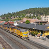 An Eastbound manifest train is seen passing the Southern Pacific depot in downtown Truckee, CA on a clear summer morning. The depot now serves as an Amtrak stop for the California Zephyr, 8-19-21