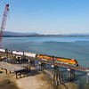 """A Westbound freight is seen about to cross the 4800-foot bridge over Lake Pend Oreille in Sandpoint, Idaho. The crane is in place building a parallel bridge to double-track the line and reduce congestion at the """"funnel."""" 4-6-21."""