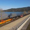 """An Eastbound tank train is seen just after crossing Lake Pend Oreille in Sandpoint, Idaho. The widened right of way and the crane in the background are part of the ongoing project to double-track the line and reduce congestion at the """"funnel,"""" 4-6-21."""