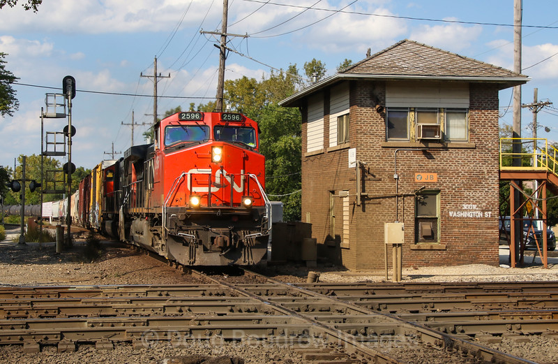 Southbound freight passes JB tower and crosses the diamond over the UP main in West Chicago on a busy Monday afternoon, 9-17-18.